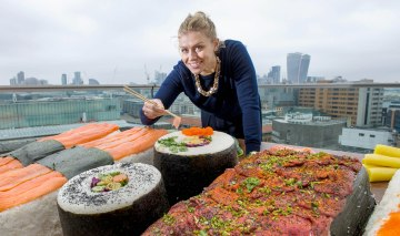 EDITORIAL USE ONLYHannah Warmington interacts with the worldÕs biggest bento box, which has been commissioned by Groupon to celebrate the capitalÕs love of sushi, London. PRESS ASSOCIATION Photo. Issue date: Wednesday September 21, 2016. Research by Groupon found that sushi is a favourite dish of residents in the capital, and tops the list for the City of London. The platter, which comprises of 350 kilos of rice and 6 sides of salmon, took 4 people, 4 days to complete. Photo credit should read: Anthony Upton/PA Wire