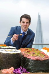 EDITORIAL USE ONLY Edward Hopkins interacts with the worldÕs biggest bento box, which has been commissioned by Groupon to celebrate the capitalÕs love of sushi, London. PRESS ASSOCIATION Photo. PRESS ASSOCIATION Photo. Issue date: Wednesday September 21, 2016. Research by Groupon found that sushi is a favourite dish of residents in the capital, and tops the list for the City of London. The platter, which comprises of 350 kilos of rice and 6 sides of salmon, took 4 people, 4 days to complete. Photo credit should read: Anthony Upton/PA Wire